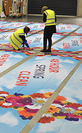People in the banner sign factory making your advertising bright with flowers for spring clean special event.