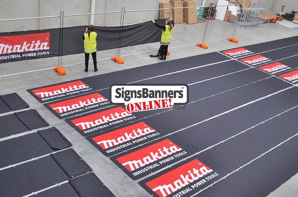 Big banners produced in bulk. People fitting and inspecting the printed banner signs inside the factory for ship out to Makita Promotional Events