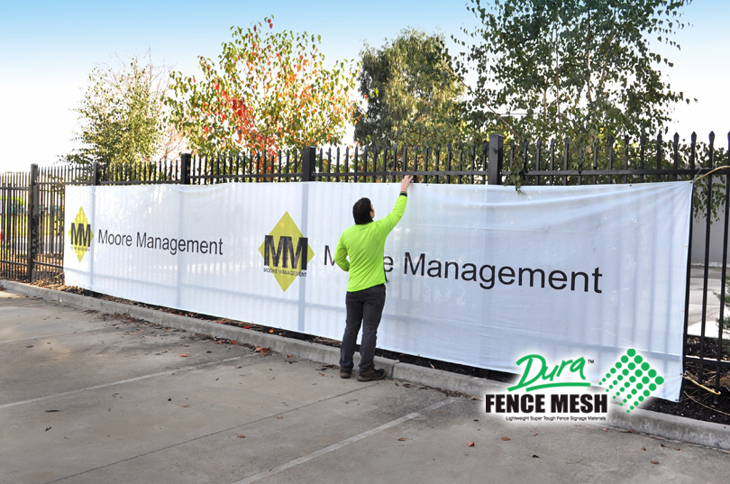 Site screens for temporary fence hire, large printed fence mesh banner fitted. White with company logo printed on banner.
