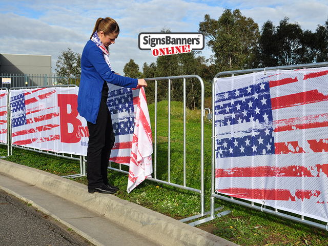 Showing the picture quality of the printed Sports Mesh as used for Baltimore events and public display steel barricades. The young lady is fitting the banner sign to the barricade