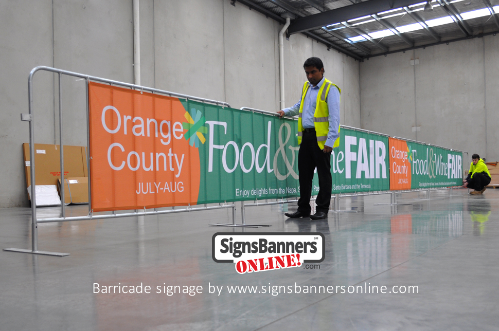 Imatges visualment Barricade signage. Barricade signage is a popular form to promote events and logos and is now very cheap. The benefits include NO SCRATCH which means that your banner signs can be stored and used annually like this example for Orange County CA event barricade cover graphics