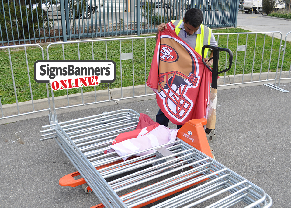 Rental fence erection panels are sitting on the trolley jack lift with fence and banner in the background