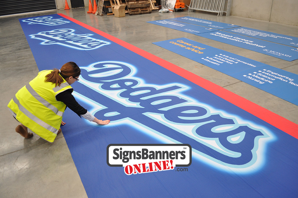 Large repeat logo style outdoor banner sign for a LA Dodgers event. Inspecting the Dodgers banner before ship out for an event. Large banner sign made from lightweight super strong polyester weave with tiny air holes.