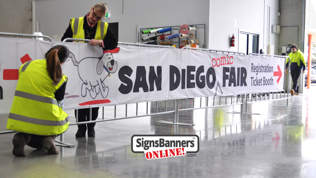 Event graphics team putting up the San Diego banner signs on the temporary event fence covers pre ship out.