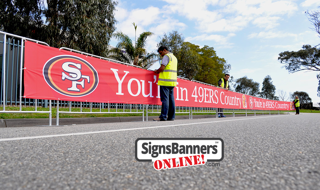 Event graphics team putting up the 49ers banner signs on the temporary event fence covers.