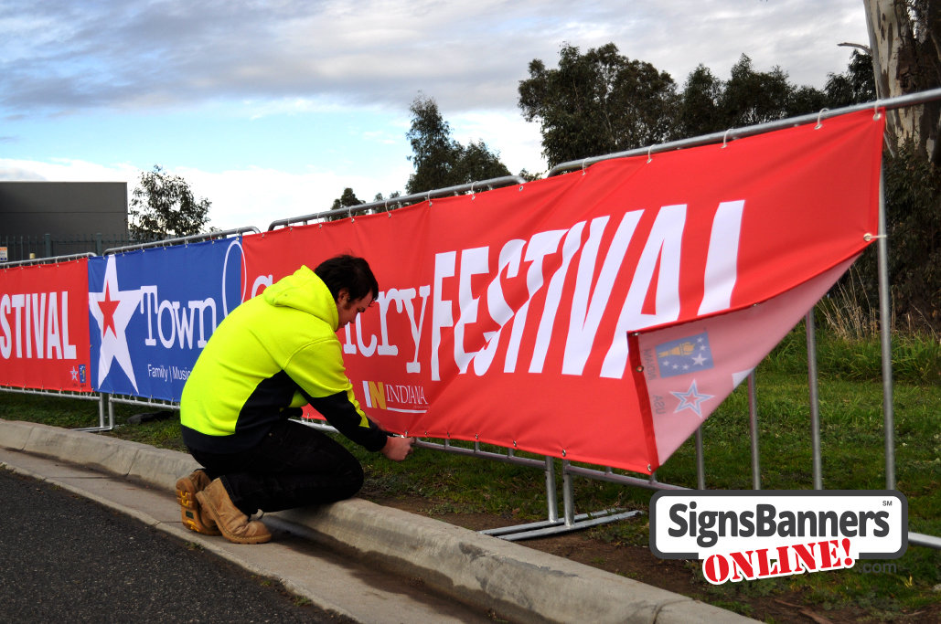 Shows the best technique for mounting banner signs onto barricade style fences as used at events and festivals usa.