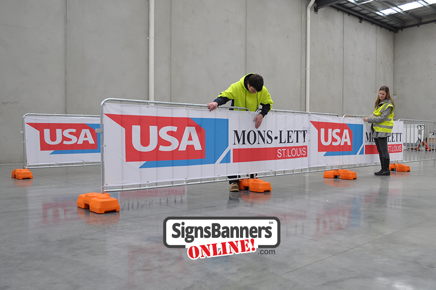 Event team installing the rent a fence banner covers for advertising a promoter