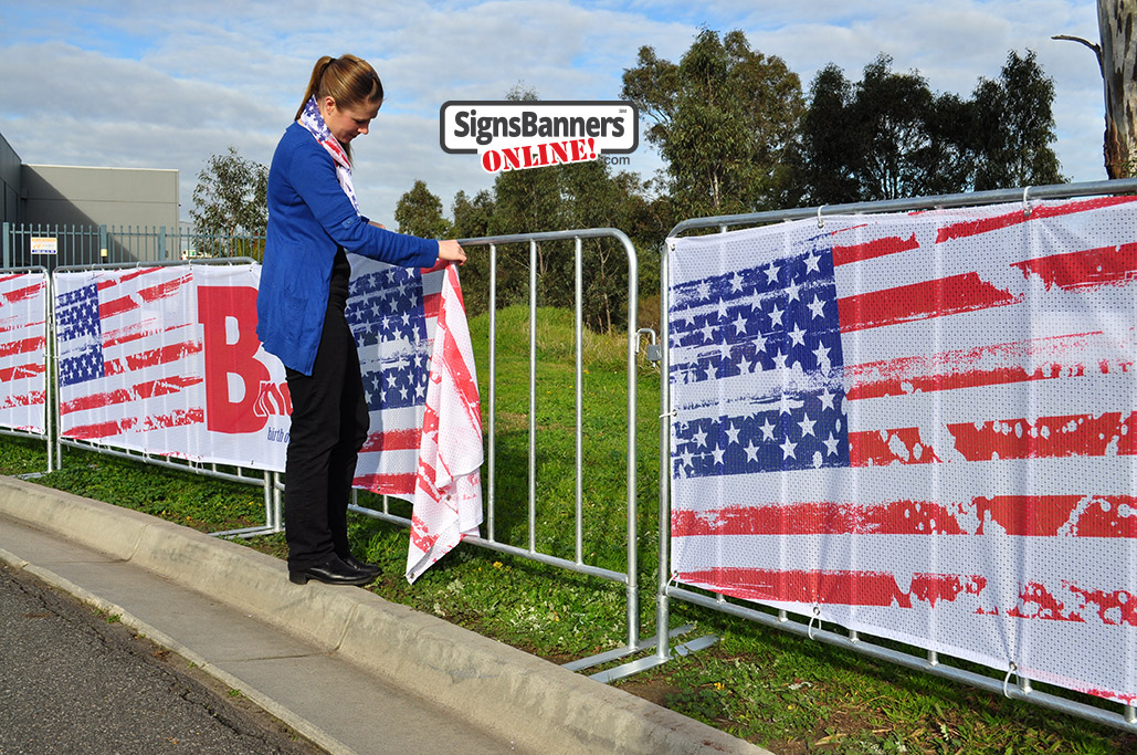 Showing the picture quality of the printed Sports Mesh as used for Baltimore events and public display steel barricades. The young lady is fitting the banner sign to the barricade.