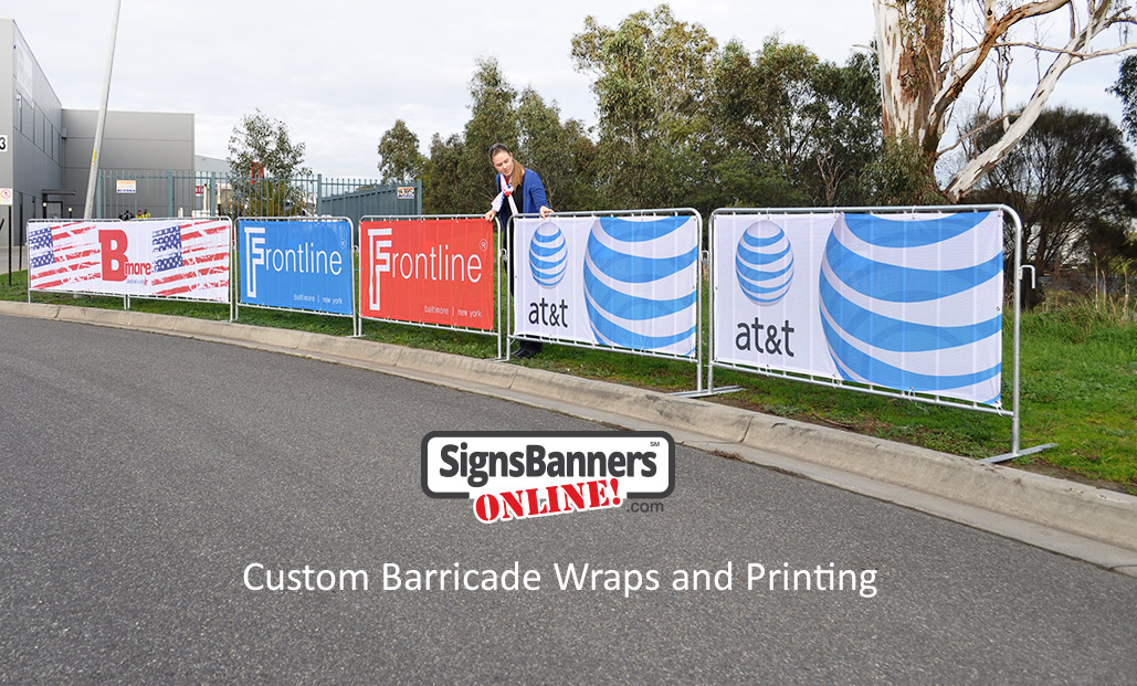 Custom barricade wraps (banner signs fitted to crowd control fence systems) set up on the street ready for an event.