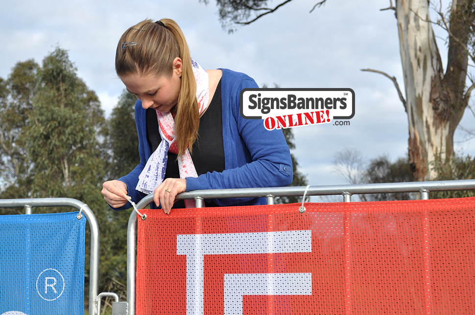 Event signage printing on the corner of the portable barricade being tied using a cable tie commonly known as Zip Tie